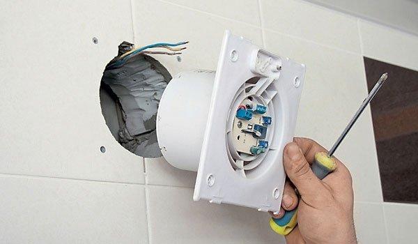 процесс установки вытяжного вентилятора в вентиляционное отверстие