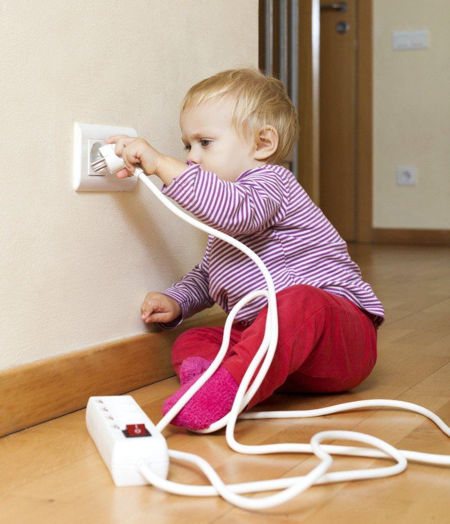 ребенок играет с электрическим удлинителем
