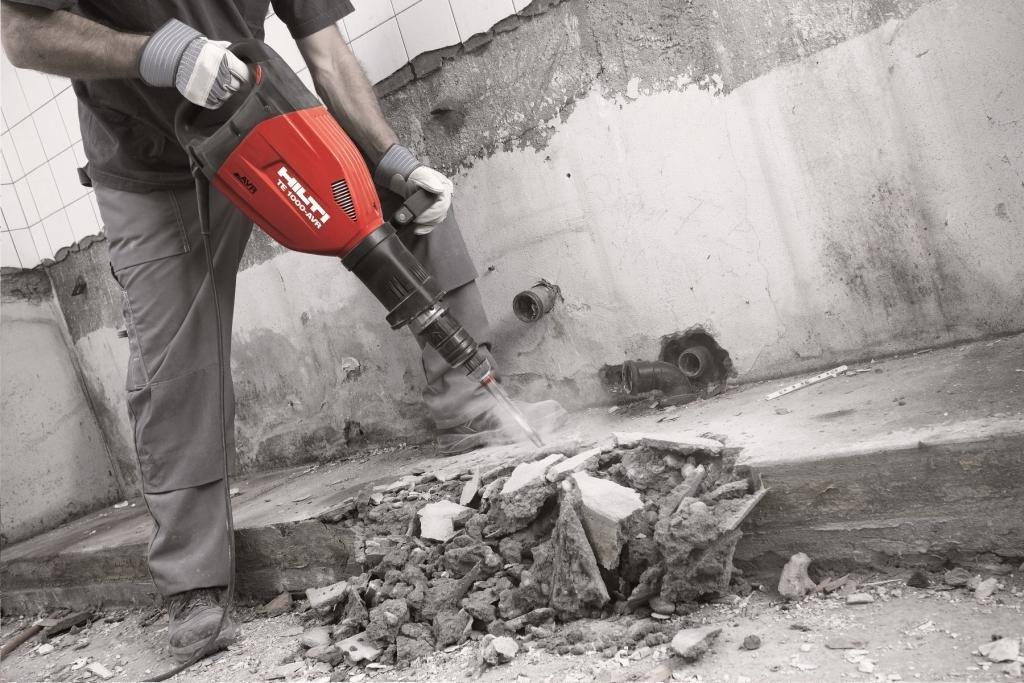 Процесс демонтажа стяжки с помощью отбойного молотка