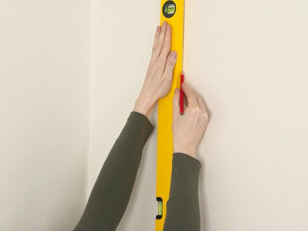 разметка стен с помощью строительной линейки