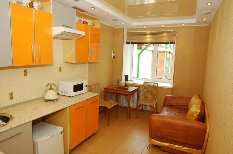 Светлый глянцевый потолок – отличное решение для маленькой кухни