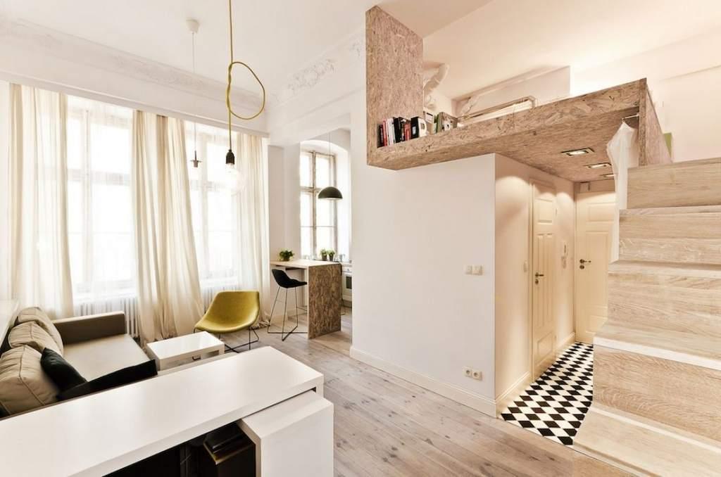 Высоко поднятое спальное место помогает эффективнее организовать пространство в квартире-студии