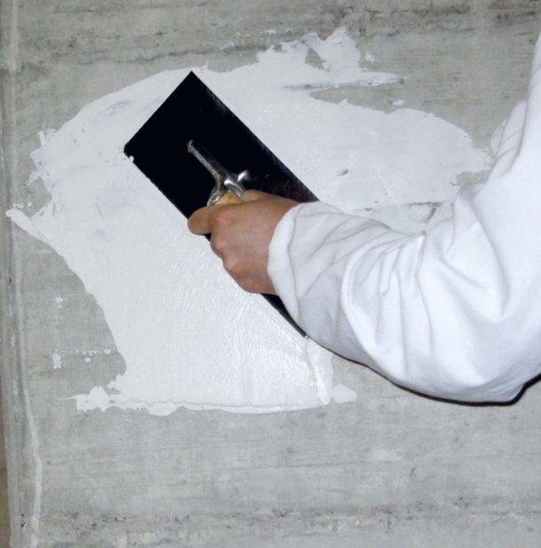 Нанесение гипсового раствора на участок стены с углублением