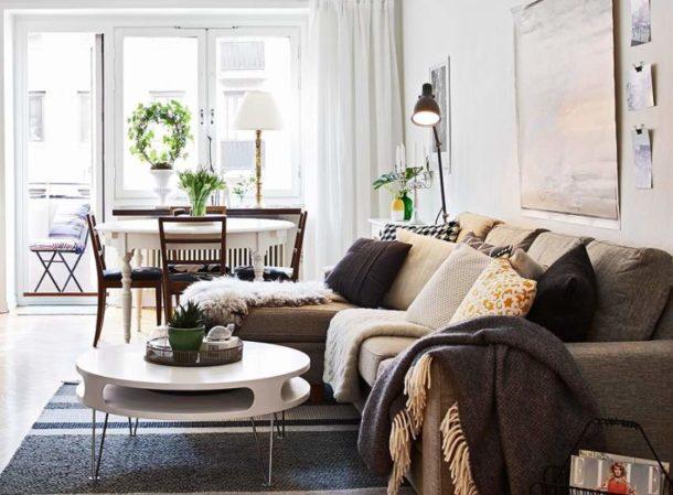 Уютный текстиль в теплых тонах разбавляет холодный белый цвет