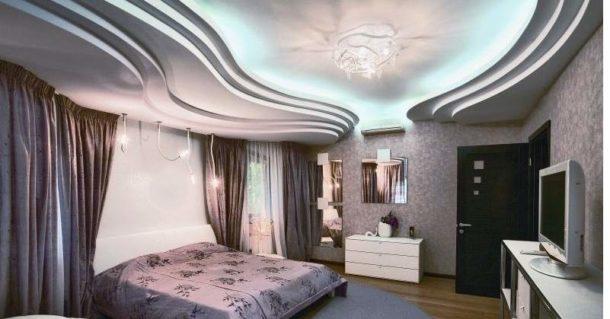 Большая спальная комната со сложной многоуровневой потолочной конструкцией