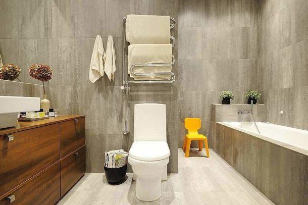 Голый бетон создает неблагоприятную атмосферу в ванной, поэтому можно использовать имитирующую его плитку